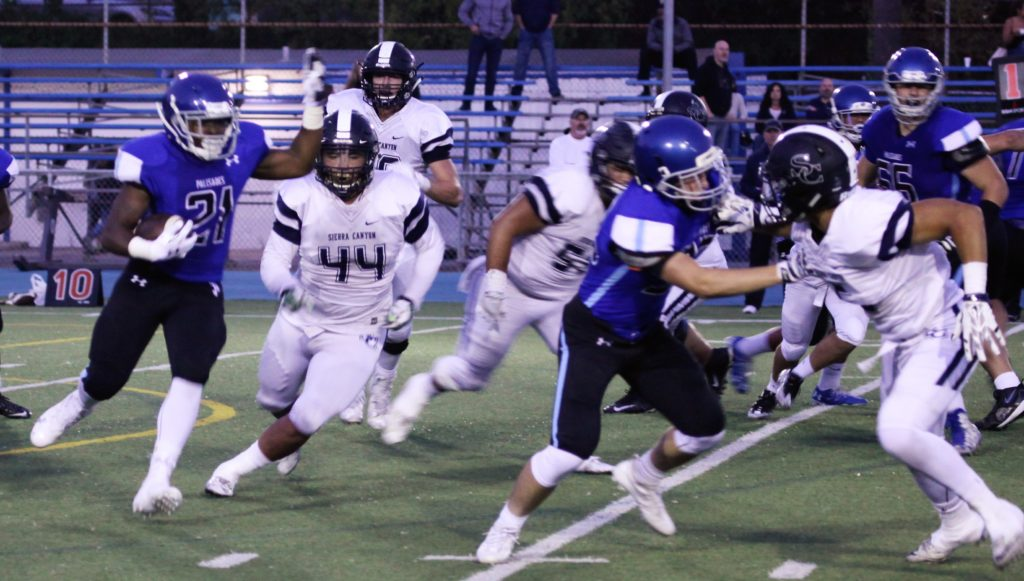 Running back Stone Maderer looks to slip by the Sierra Canyon defense.