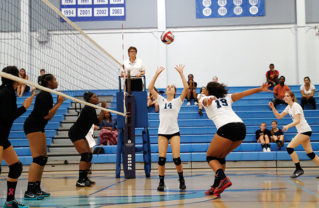 Sophomore Keely McMahon sets the ball for senior Angel Echipue. Photo: Will Schwerdtfeger
