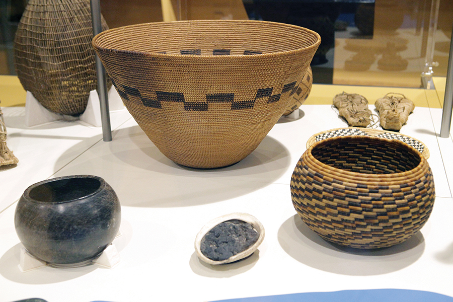 This exhibition display case features Tongva objects used for everyday activities. Lower foreground: Steatite (soapstone) bowl, 1500s-1800s, courtesy James W. Calkins Collection; Center foreground: Abalone container for asphalt (pre-concrete), courtesy, Burnham Chappelle American Collection. Foreground right: Tongva basket bowl, late 1800s, donated to the Southwest Museum of the American Indian by Miss Ethel R. Shorb. Center: Basket made from sumac, deer grass and juncus.
